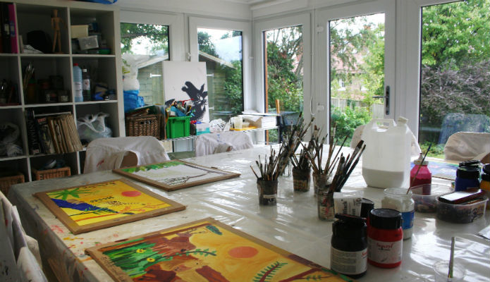 A large paint table with a garden room used for teaching young children