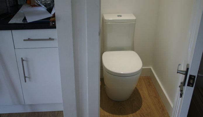 Photograph of compact toilet within a large garden room