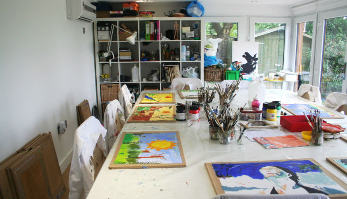 Large table within a garden room which is used for teaching young children how to paint